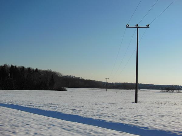 Eine Winterlandschaft: Zu sehen ist auch eine Stromtrasse mit einem Strommast