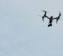 Eine Kamera-Drohne fliegt am Himmel.